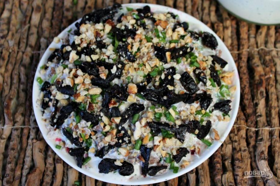 Нарезаем чернослив небольшими кусочками и выкладываем сверху на салат, добавляем колотые грецкие орехи.