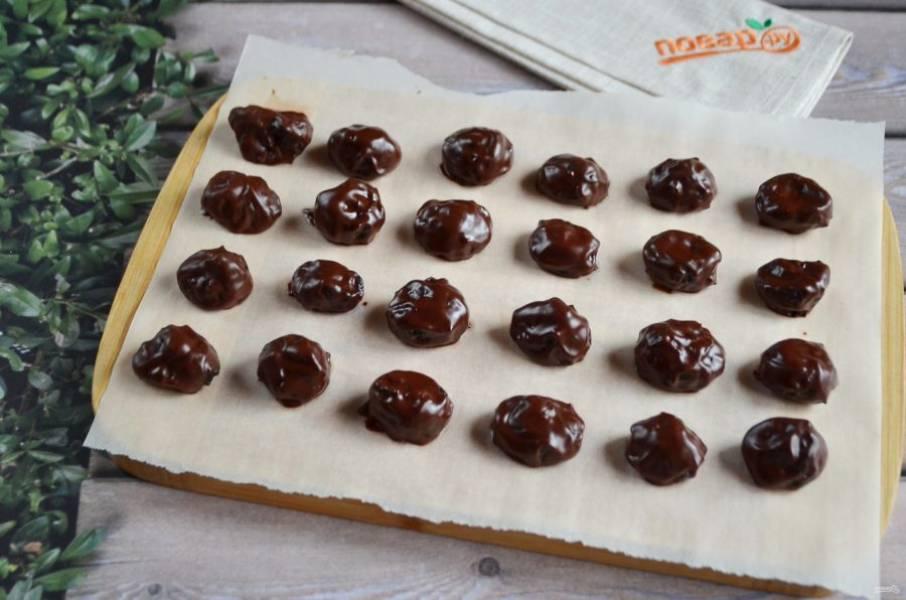 6. Разделочную кухонную доску (или поднос) застелите пергаментной бумагой и выкладывайте на неё готовые конфеты. После того, как все черносливины будут в шоколаде, уберите лакомство в холодильник на 1 час для застывания.
