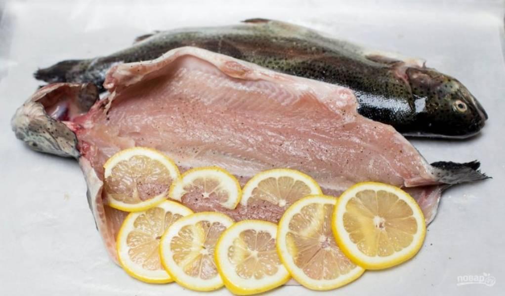 Промажьте форель солью и перцем. В центр уложите дольки лимона.