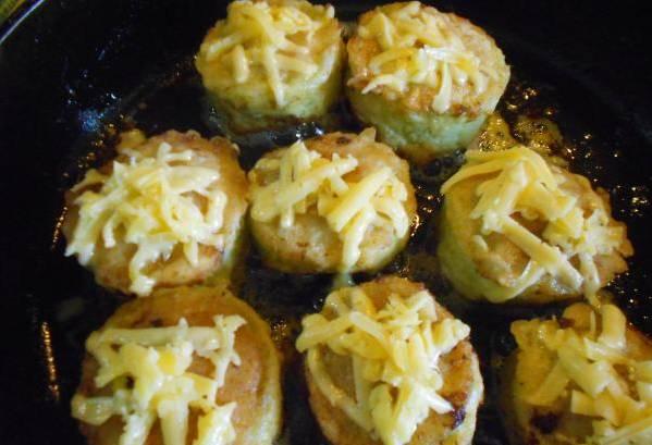 3. Теперь каждый кусочек кабачка наполним фаршем и обмакнем в взбитое с майонезом яйцо. Поместим на сковородку, и тушим на маленьком огне до готовности. Переворачиваем несколько раз. В конце посыпаем тертым сыром и ждем, пока расплавится.