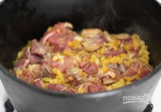 2. Разогрейте масло и обжарьте на сильном огне мясо до образования корочки. Добавьте лук, чеснок, имбирь, шафран. На среднем огне обжарьте еще пару минут.