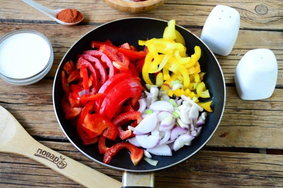 Выложите перец в сковороду вместе с порезанным полукольцами луком. Немного обжарьте на медленном огне.