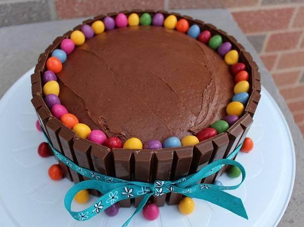4. Украсить торт для мамы в домашних условиях можно чем угодно - кремом, мастикой, ягодами. Но наиболее простой и очень яркий вариант - это разноцветные конфетки. Их нужно выложить по кругу на краях торта.