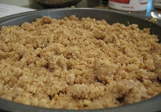 7. Полученную крошку распределить по поверхности и отправить форму в разогретую духовку. Выпекать сладкий пирог с вареньем в домашних условиях около 25 минут.