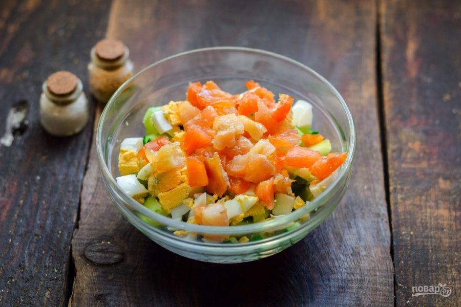 Копченую семгу также нарежьте небольшими кубиками и переложите в салат.