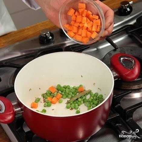 Добавьте горох, через 3 минуты добавьте морковь. Обжарьте пару минут.