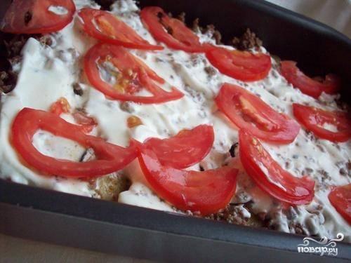 Заливаем подсоленной сметаной и кладем слой помидоров.