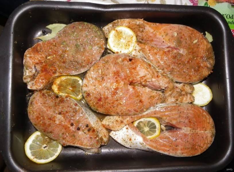 Стейки промажьте солью, перцем и специями. Уложите их на противень, смазанный маслом. Сверху рыбу сбрызните соком лимона, а  кружочки этого цитруса разложите по всей поверхности рыбы. Добавьте лавровый лист и перец горошком.