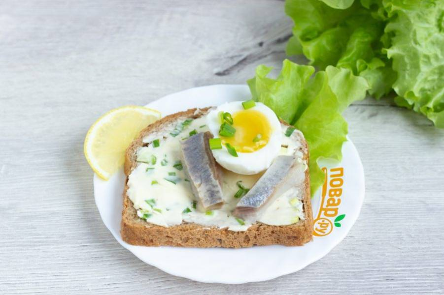К сельди положите половинку яйца, блюдо украсьте листьями салата и ломтиками лимона. На яйцо и хлеб посыпьте немного рубленного зеленого лука.