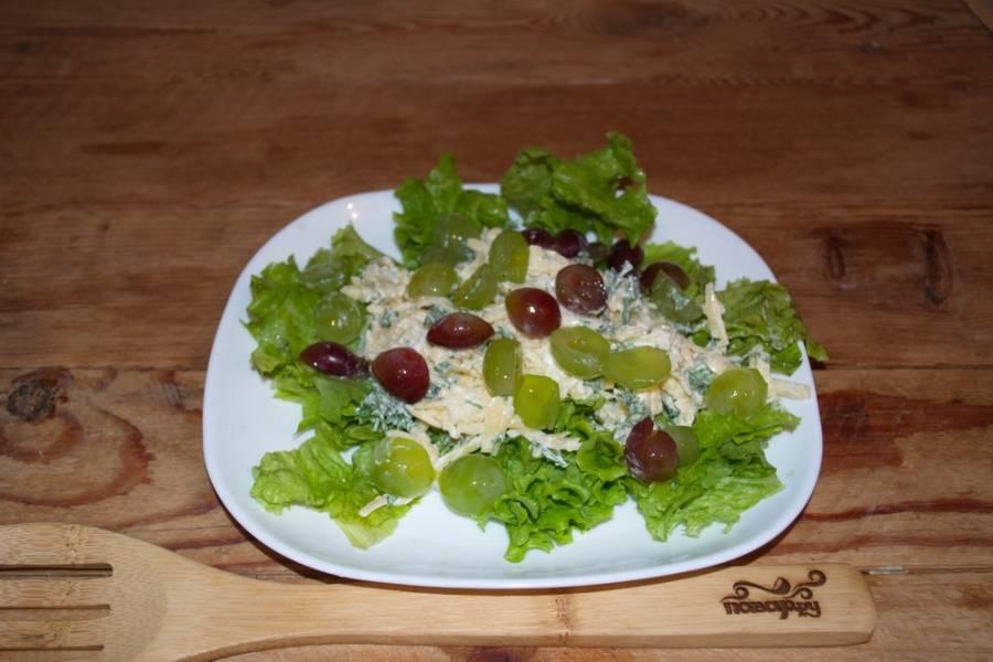Заправьте сыр с зеленью майонезом. Перемешайте. Выдавите через пресс чеснок — и снова перемешайте. Выложите сырную массу на салатные листья. Сверху уложите половинки винограда.