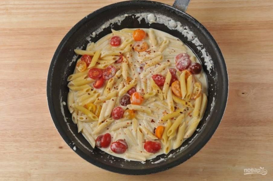 4. На другой сковороде разогрейте немного масла. Обжарьте в нём чеснок (30 секунд). Далее добавьте сливки, воду от пасты и натрите пармезан. Готовьте, помешивая, 5 минут. А потом добавьте макароны и помидоры. Перемешайте, посолите и поперчите.