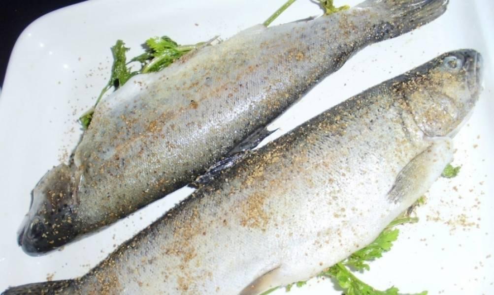 Форель вымойте, почистите, выпотрошите. Также не забудьте удалить жабры, если будете запекать рыбу целиком, с головой. Натрите рыбу специями и солью. В брюшки положите зелень.