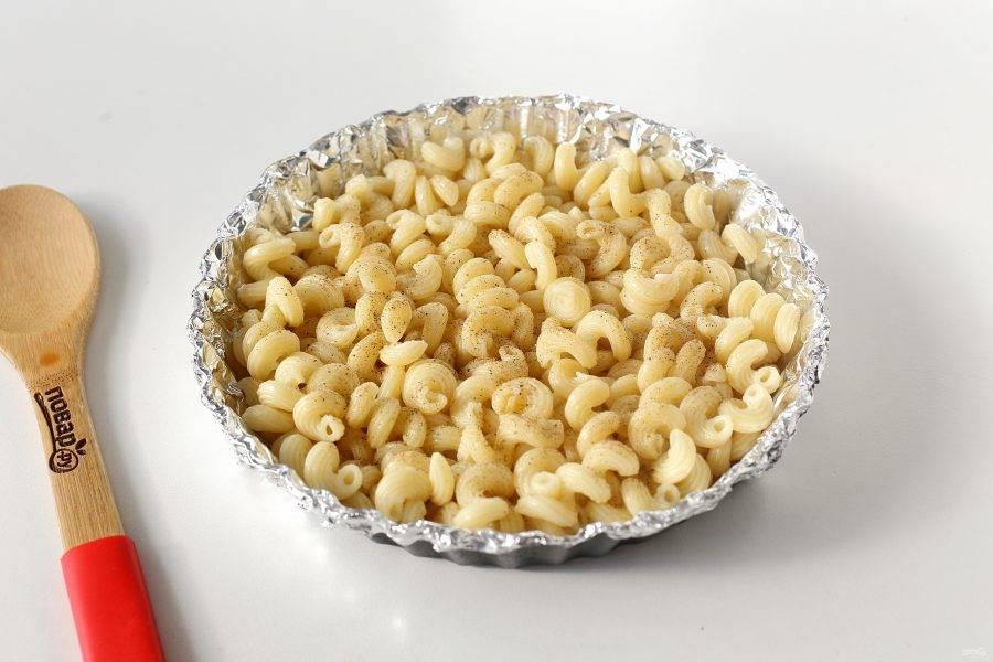 Форму для запекания смажьте маслом. Я для удобства застилаю ее предварительно фольгой. Выложите ровным слоем отварные макароны.