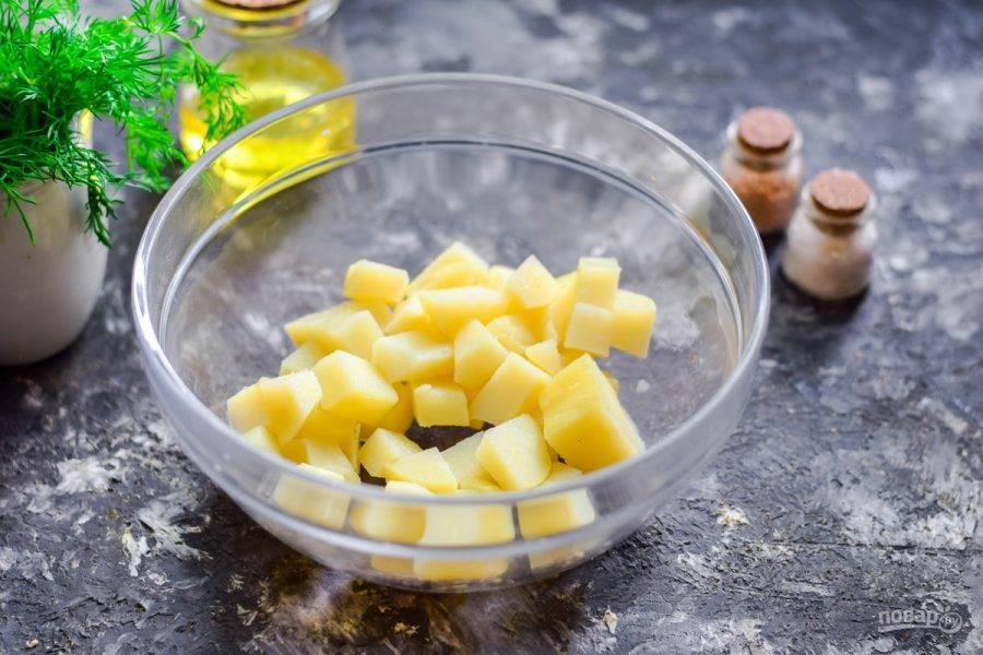 Вареный картофель очистите и нарежьте небольшими кубиками, выложите в салатник.