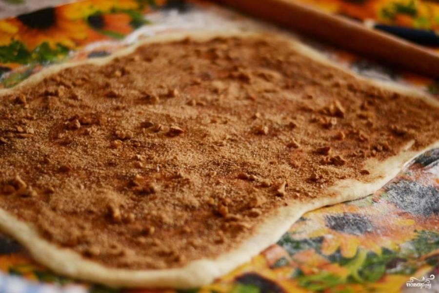 если используете замороженное тесто, то предварительно дайте ему разморозиться при комнатной температуре. Раскатайте тесто на присыпанном мукой столе в пласт 45 на 30 см (приблизительно). Смешайте корицу с 2-3 ст. л. сахара и рубленными грецкими орехами.  Смажьте пласт растительным маслом и посыпьте равномерно смесью из корицы с орехами.