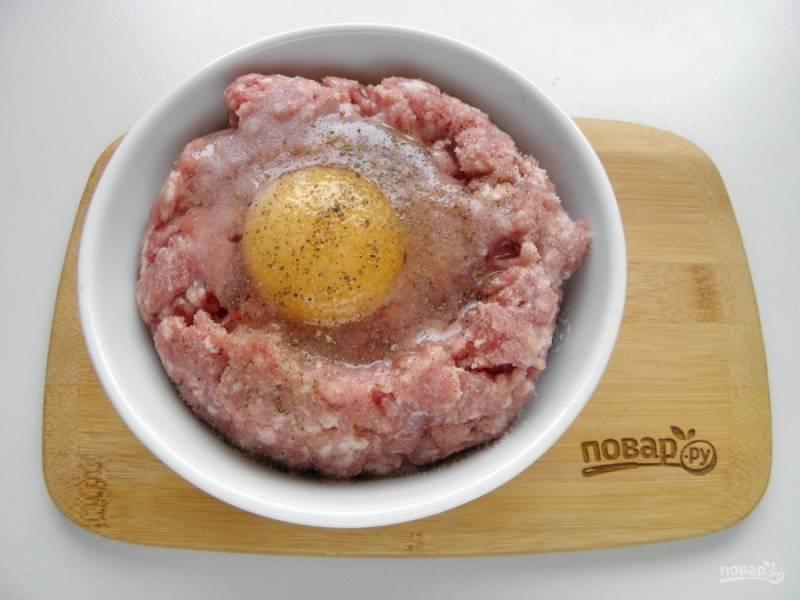 В фарш добавьте соль, перец черный молотый и сырое яйцо. Перемешайте хорошенько.