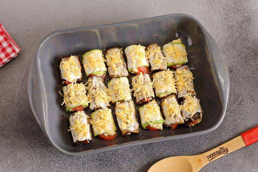 Смажьте сметаной и посыпьте оставшимся сыром. Запекайте в духовке при температуре 180 градусов около 15 минут (до мягкости).