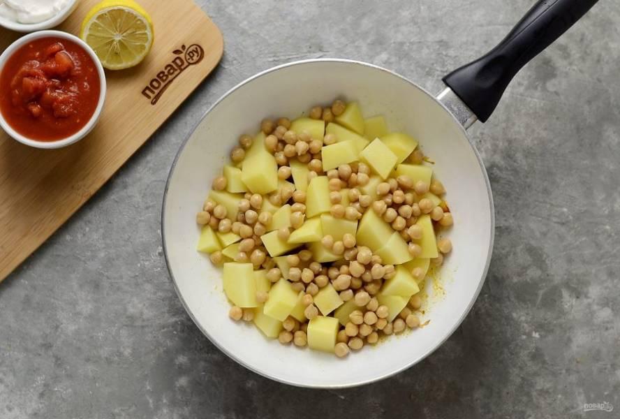 Картофель очистите, нарежьте кубиками. Добавьте в сковороду вместе с консервированным нутом. Обжарьте 3-5 минут.