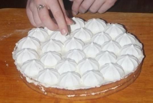 2. Берем готовый корж, промазываем его сливками и выкладываем безе, а сверху накрываем вторым коржом.