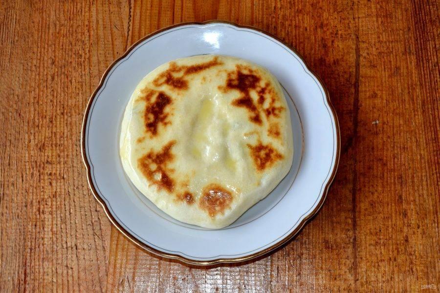 Жарьте хачапури с двух сторон до румяности по 3-4 минуты. После выложите на тарелку и смажьте растопленным сливочным маслом.