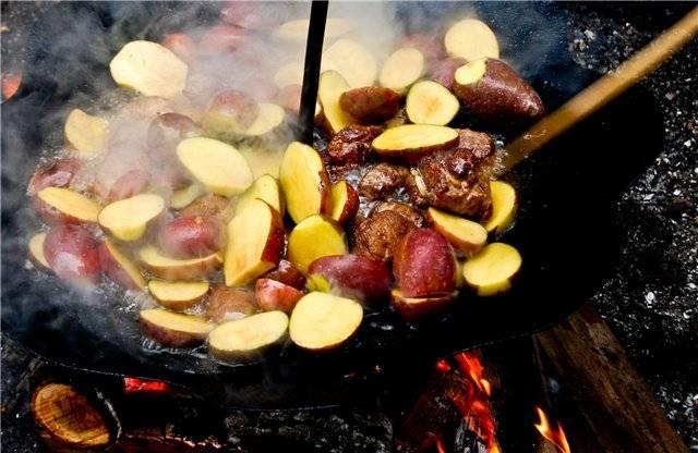 Когда мяско приобретает красивый золотистый оттенок, выкладываем картофель. ВНИМАНИЕ! Если картофель не для запекания, его нежно очистить от кожуры.