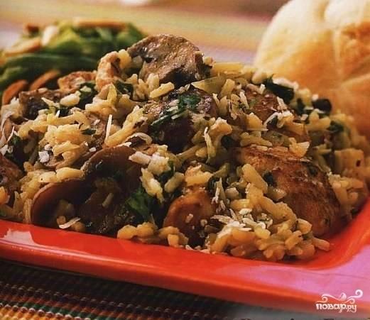 Попробовать рис - если он почти готов, выложить поверх него грибы, закрыть крышкой, выключить огонь и дать плову дойти минут 15.  Перед подачей на стол плов перемешать. Выложить на плоское блюдо и подавать горячим.