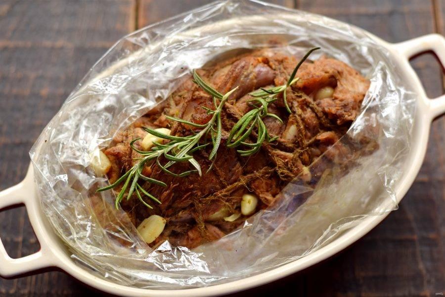 После мясо переложите в рукав для запекания. Для аромата добавьте несколько веточек розмарина.