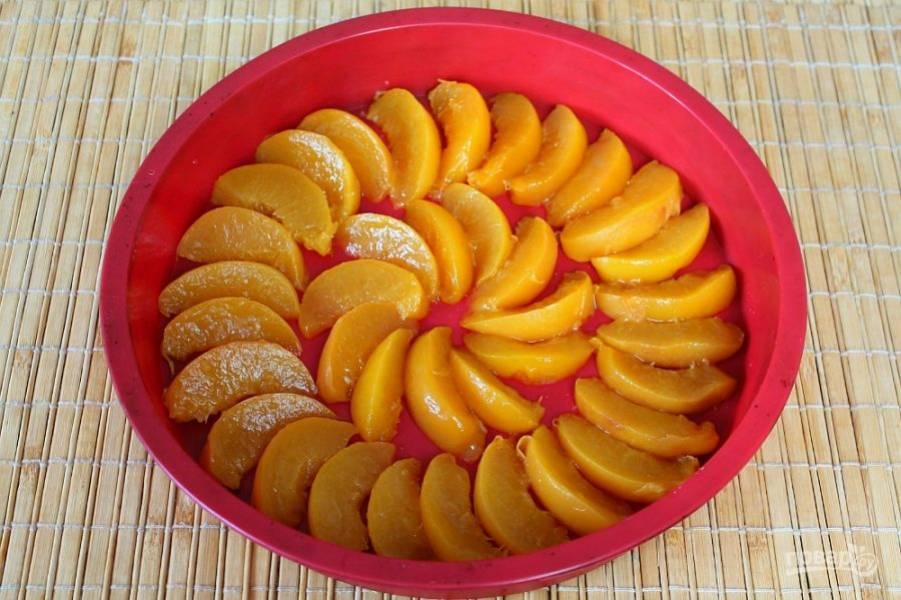Персики режем дольками и выкладываем на дно формы.