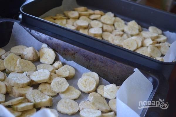 1. Первым делом покажу, как сделать в домашних условиях банановую муку. Очистите бананы, нарежьте их тонкими кружочками. Выложите на противень, застеленный пергаментом. Отправьте в духовку и сушите 2-3 часа при самой минимальной температуре. Также удобно использовать сушилку для овощей и фруктов. Летом можно высушить на солнце.