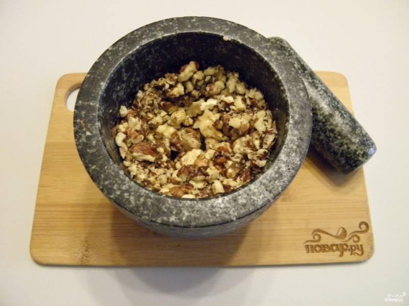 Грецкие орехи освободите от скорлупы. Подавите их в ступке, только не мелко, чтобы в готовой колбаске были видны кусочки.