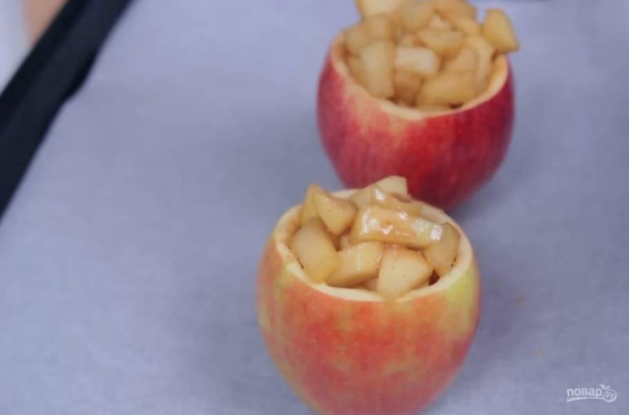 4. На среднем огне растопите сахар и дайте яблокам закарамелизоваться, чтобы они слегка размягчились (примерно 5 минут). Формы из яблок выложите на застеленный пергаментной бумагой противень и заполните их яблоками из карамели.