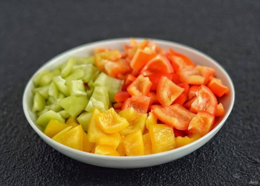 У болгарских перцев отрежьте хвостики, удалите сердцевину и перегородки. Нарежьте на ломтики среднего размера.