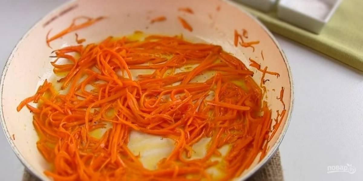 2. Добавьте уксус, приправу и перемешайте. Морковь также натрите тонкой соломкой. Разогрейте на среднем огне растительное масло. Обжарьте морковь в течение 2-3 минут на среднем огне.
