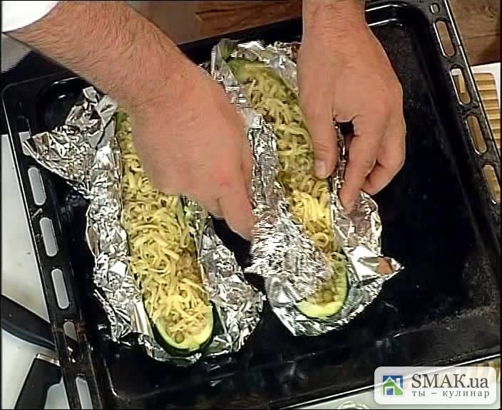 Разложите кабачки на столе. Ложкой закладываем в них начинку со сковородки. Присыпаем тертым сыром. Заматываем все это дело фольгой и ставим в духовку на 15 минут. Температуру выставляем 220 градусов.