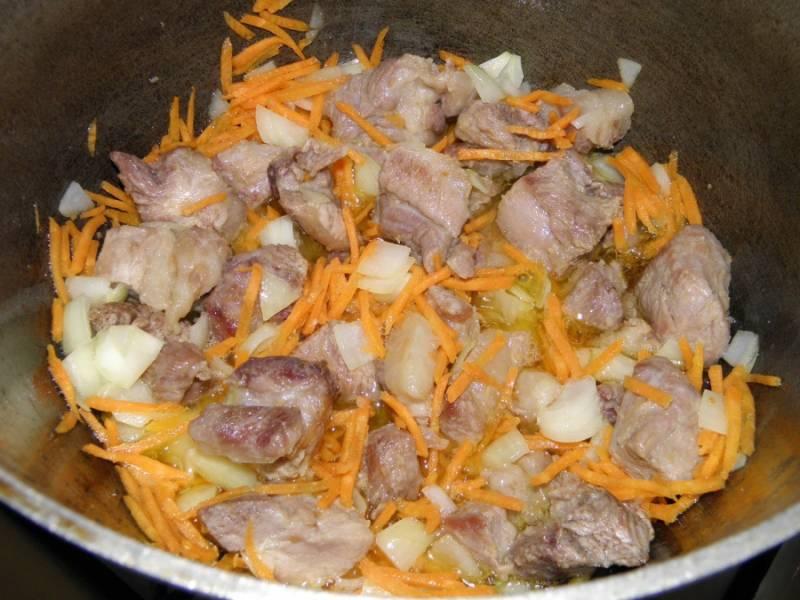 7. К обжаренному мясу добавьте лук и морковь, обжарьте все вместе до золотистого цвета моркови.