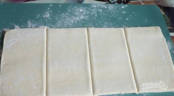 Размораживаем тесто, слегка раскатываем его на столе, присыпанном мукой. Разделите пласт теста на четыре прямоугольника.
