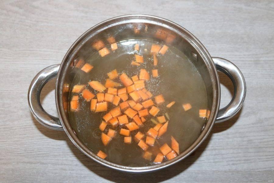 Поставьте на плите воду или бульон, доведите до кипения, добавьте морковь.
