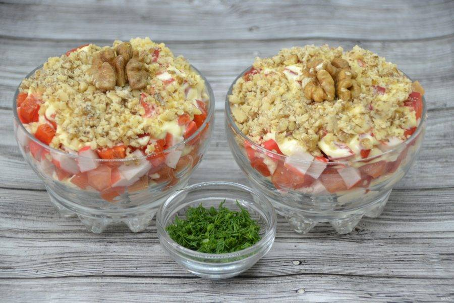 Украсьте верх салата ореховой крошкой, цельным ядром ореха и измельченной зеленью.