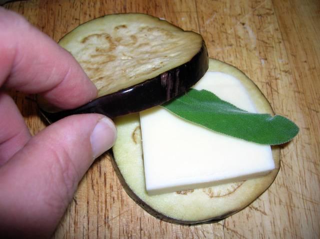 4. Сыр порежьте кусочками, величиной с кружок баклажана. На баклажан выложите сыр, выдавите небольшое количество чеснока и веточку или листик зелени. Прикройте вторым кружочком баклажана.