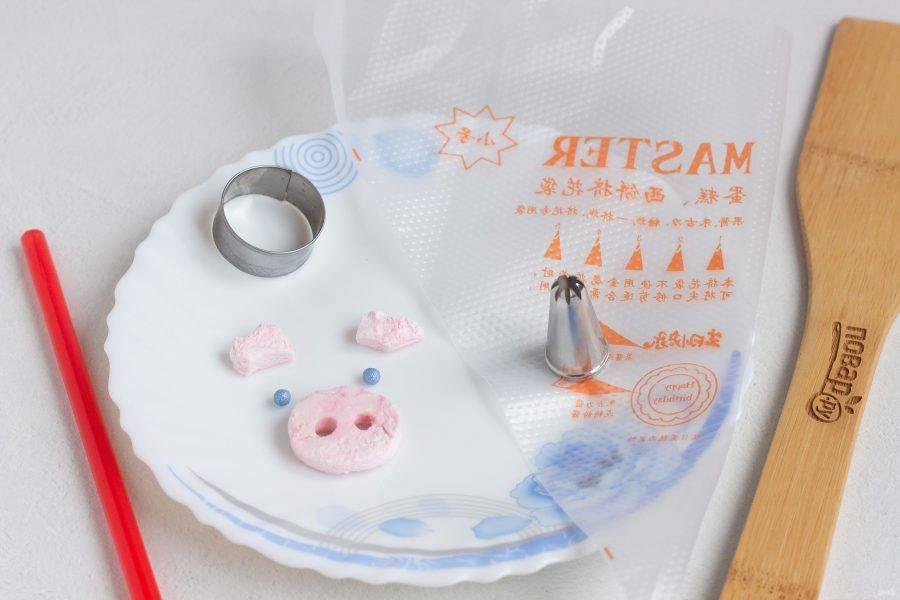 Пока остывают кексы можно подготовить вот такой декор для свинок из зефира. Зефир нарежьте острым ножом пластинами и вырезайте нужные элементы: пяточок и ушки. Для глаз я использовала кондитерские бусины, можно взять шоколадные капли. Ротик можно нарисовать пищевым фломастером или обойтись без него! Также подготовьте насадку и мешок для крема.