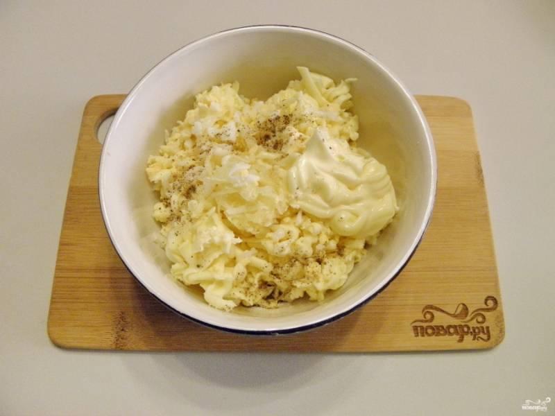 Приготовьте начинку для рулетиков. Соедините в тарелочке тертый сыр с яйцом и чесноком. Добавьте соль, перец молотый черный и майонез. Перемешайте до однородной массы.