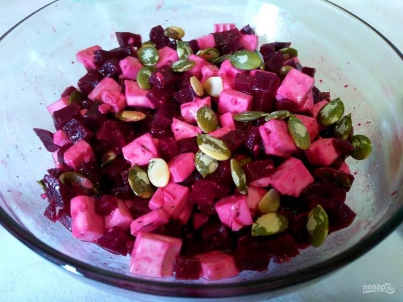 Переложите томлёную свёклу в салатник, дайте ей слегка остыть (5-10 минут) и соедините с порезанным сыром. Посолите салат, добавьте смесь специй (можно исключить или заменить небольшим количеством чёрного молотого перца). Заправьте свекольный салат соком лимона и подсолнечным маслом, добавьте тыквенные семечки и хорошо перемешайте все ингредиенты. Блюдо готово!