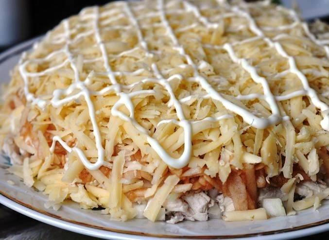 Теперь выложите ингредиенты слоями в виде горки: белки, грибы, курица, лук, яблоки, сыр. Каждый слой смазывайте майонезом.