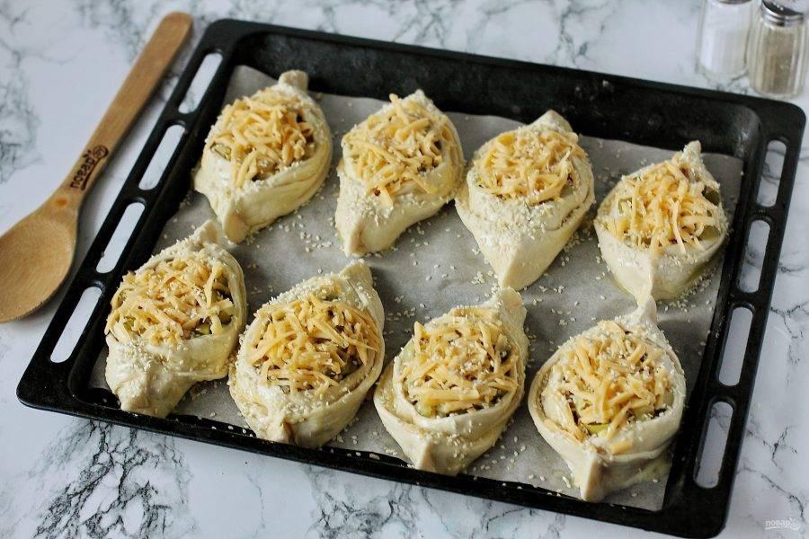 Застелите противень пекарской бумагой и выложите получившиеся лодочки. Смажьте заготовки желтком и посыпьте кунжутом. Запекайте в духовке при температуре 180-200 градусов около 20-30 минут.