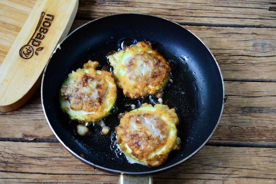 Обмакните кабачки с фаршем в кляр и выложите в сковороду с разогретым растительным маслом. Жарьте на медленном огне с обеих сторон до готовности фарша, мягкости кабачка и образования золотистой корочки.