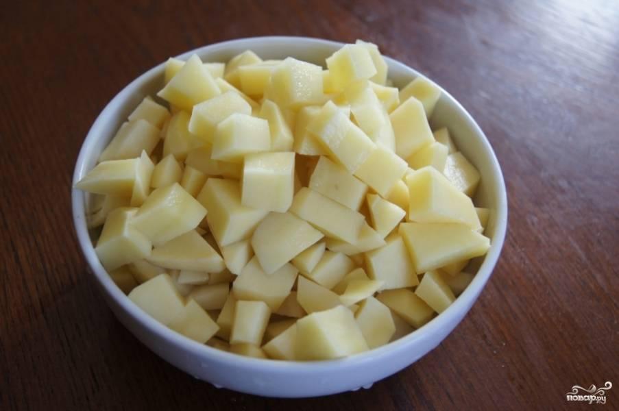 3.Картофель хорошенько промываем, удаляем черные точки. После чего чистим,  нарезаем кубиками. Выкладываем к мясу в мультиварку.