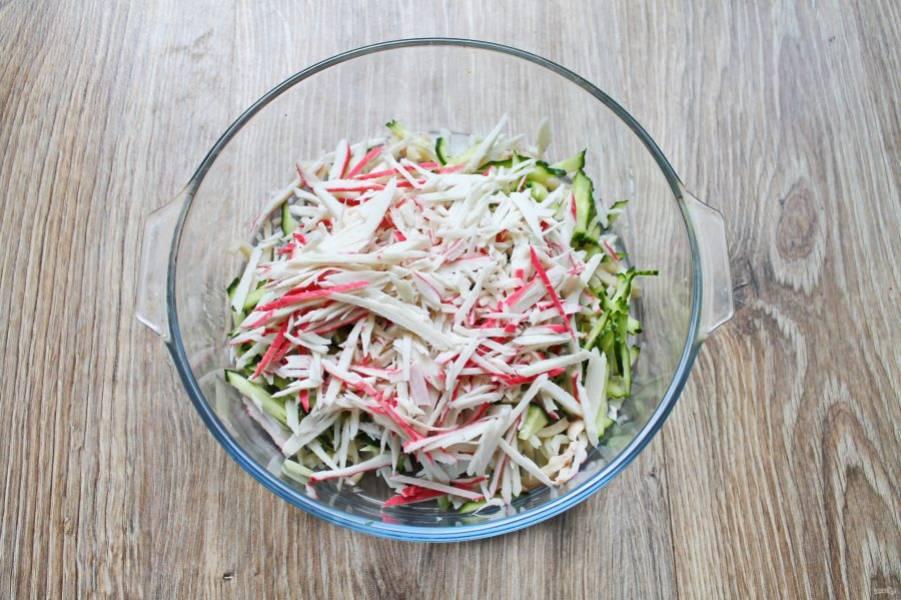 Крабовые палочки очистите от оболочки и порежьте соломкой, выложите в салат.