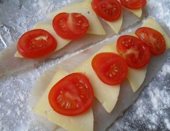 Выкладываем поверх рыбы ломтики помидор и сыра. Заворачиваем рыбу рулетиками и прижимаем друг к другу.
