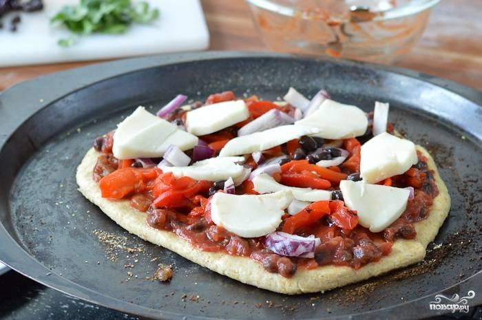 Сверху добавьте тушенный красный сладкий перец, лук, кусочки моццареллы. Отправьте в духовку на 10-15 минут до готовности.