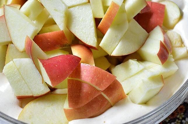 3.Нарежьте яблоки небольшими дольками. Постарайтесь это сделать быстрее, чтобы яблоки не успели потемнеть. Добавьте яблоки в тесто и немного утопите в нем.